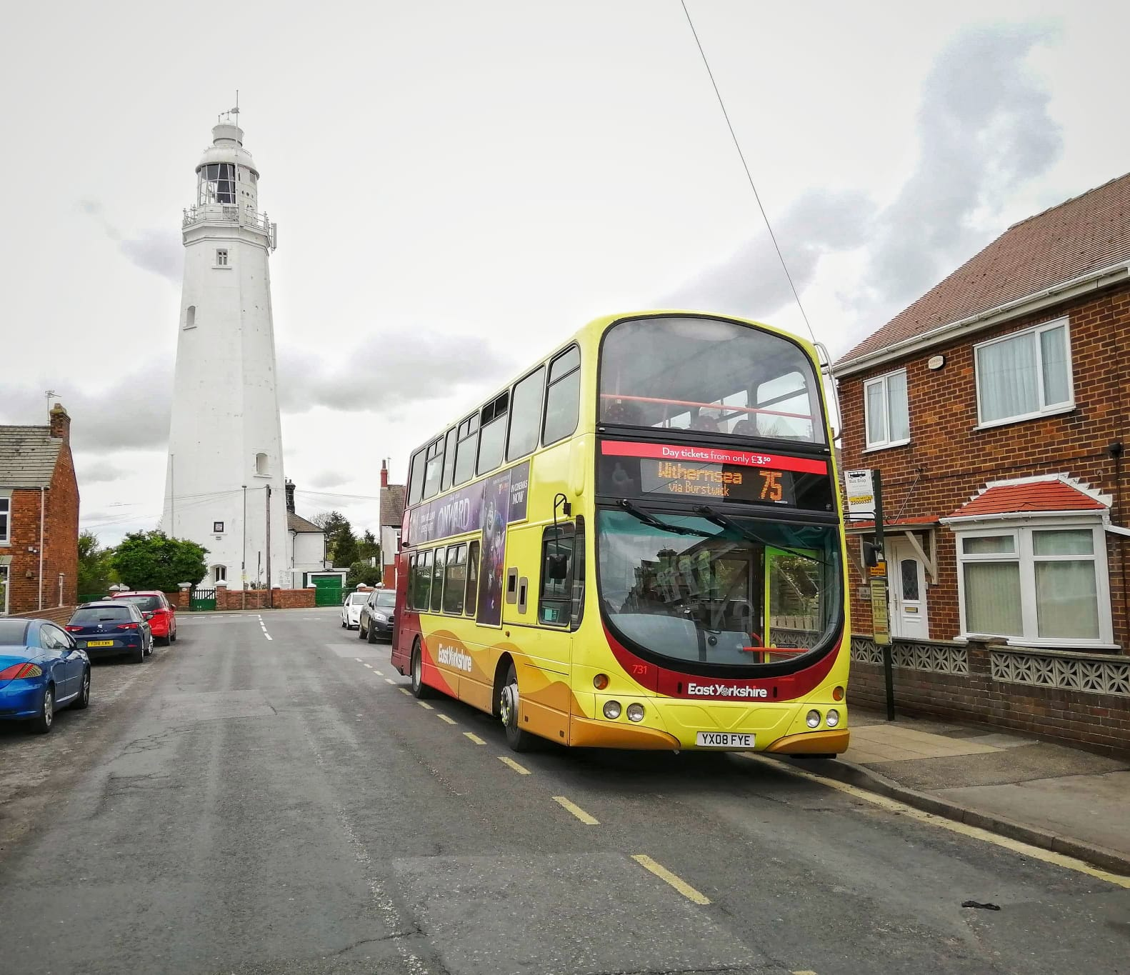 A double decker East Yorkshire bus in front of Withernsea Lighthouse