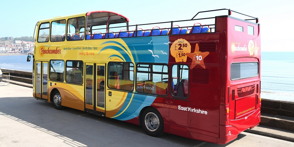 A colourful Beachcomber open top bus in front of Scarborough's South Bay