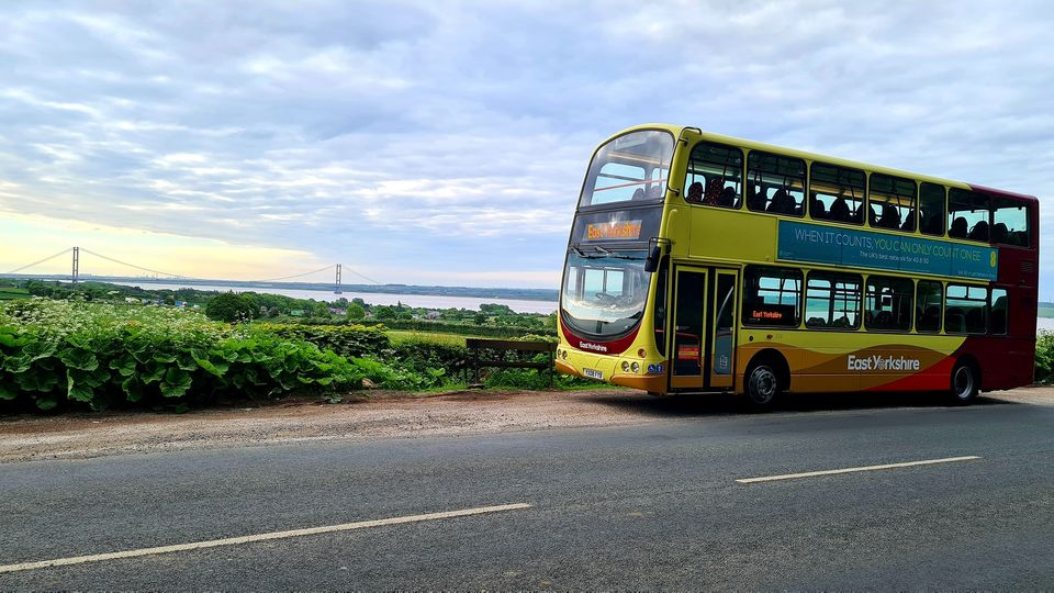 An East Yorkshire double decker bus parked on Swanland Hill with the Humber Bridge in the background