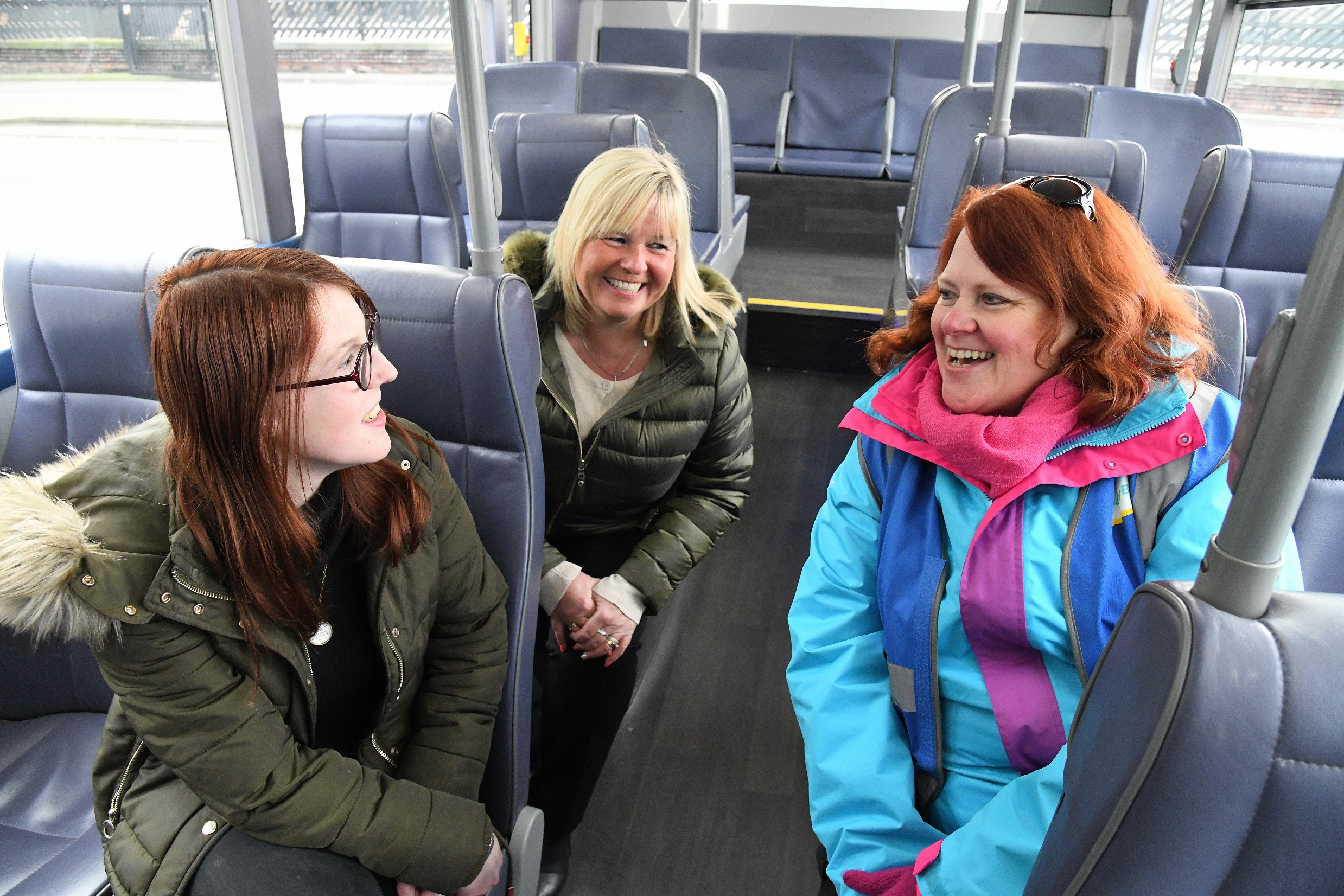A group of people chat on a bus