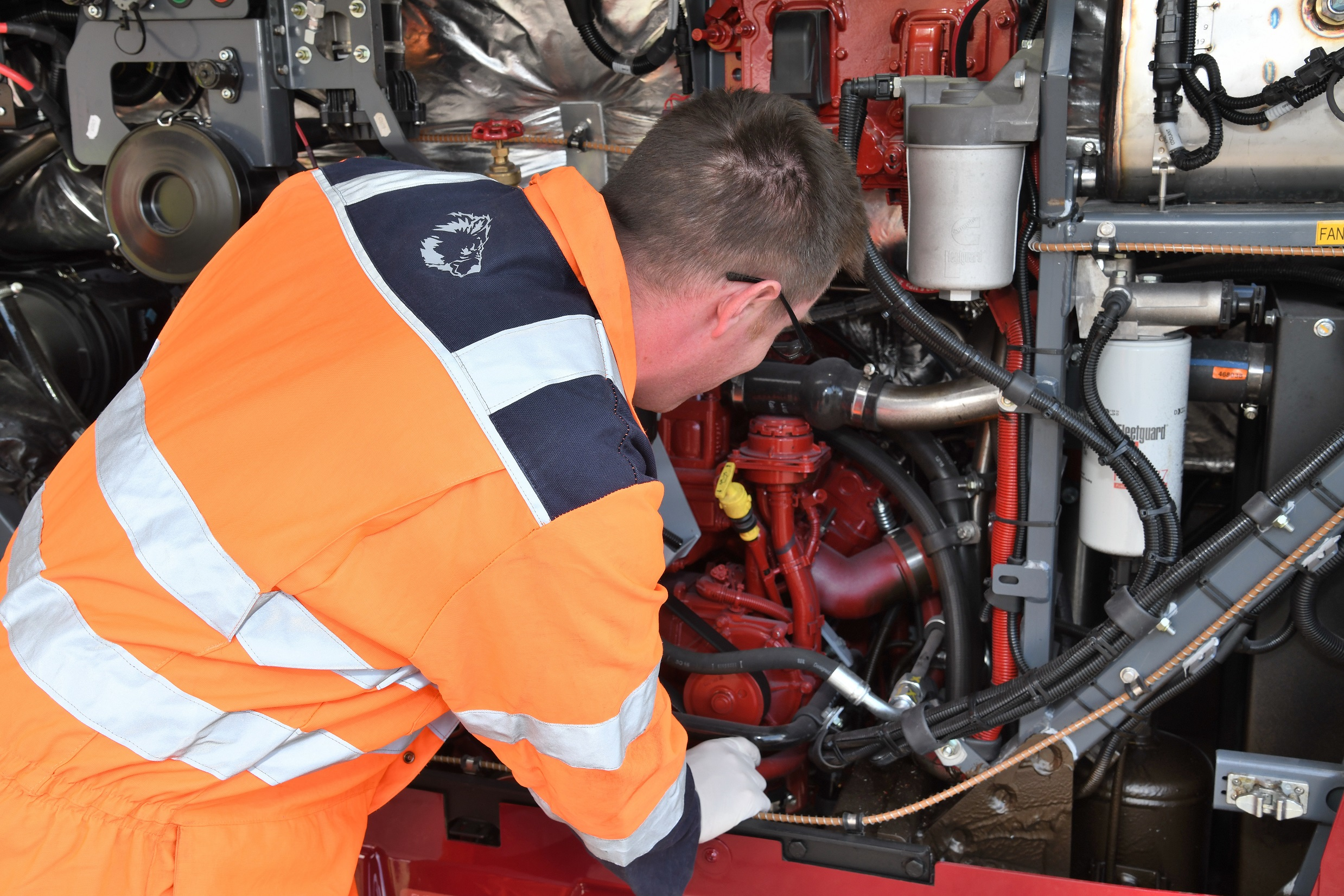 An engineer in orange overalls inspects a bus engine