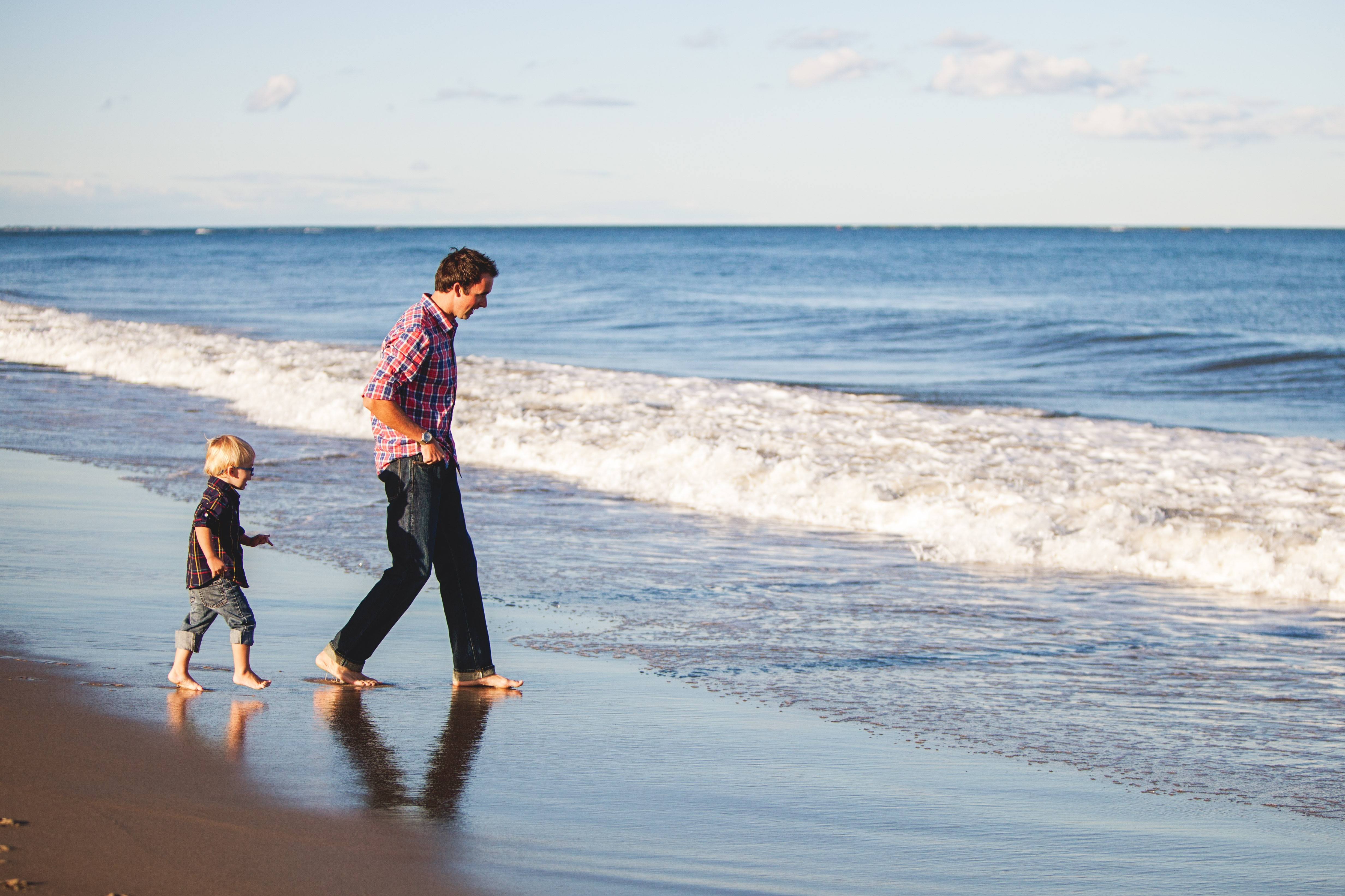 A father and son paddle in the waves at the beach