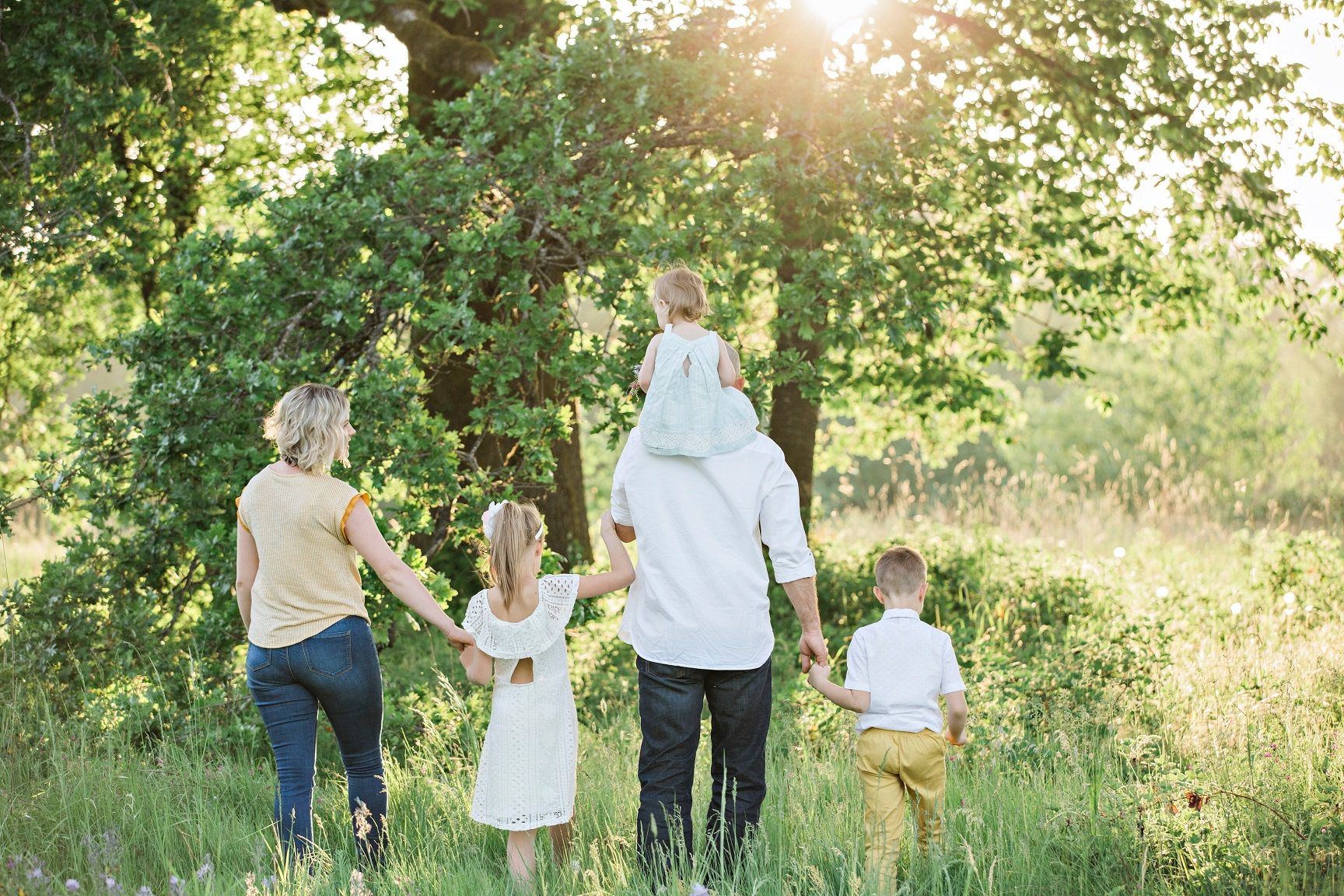 A family with three young children walk through woods, with the sunlight streaming through the trees