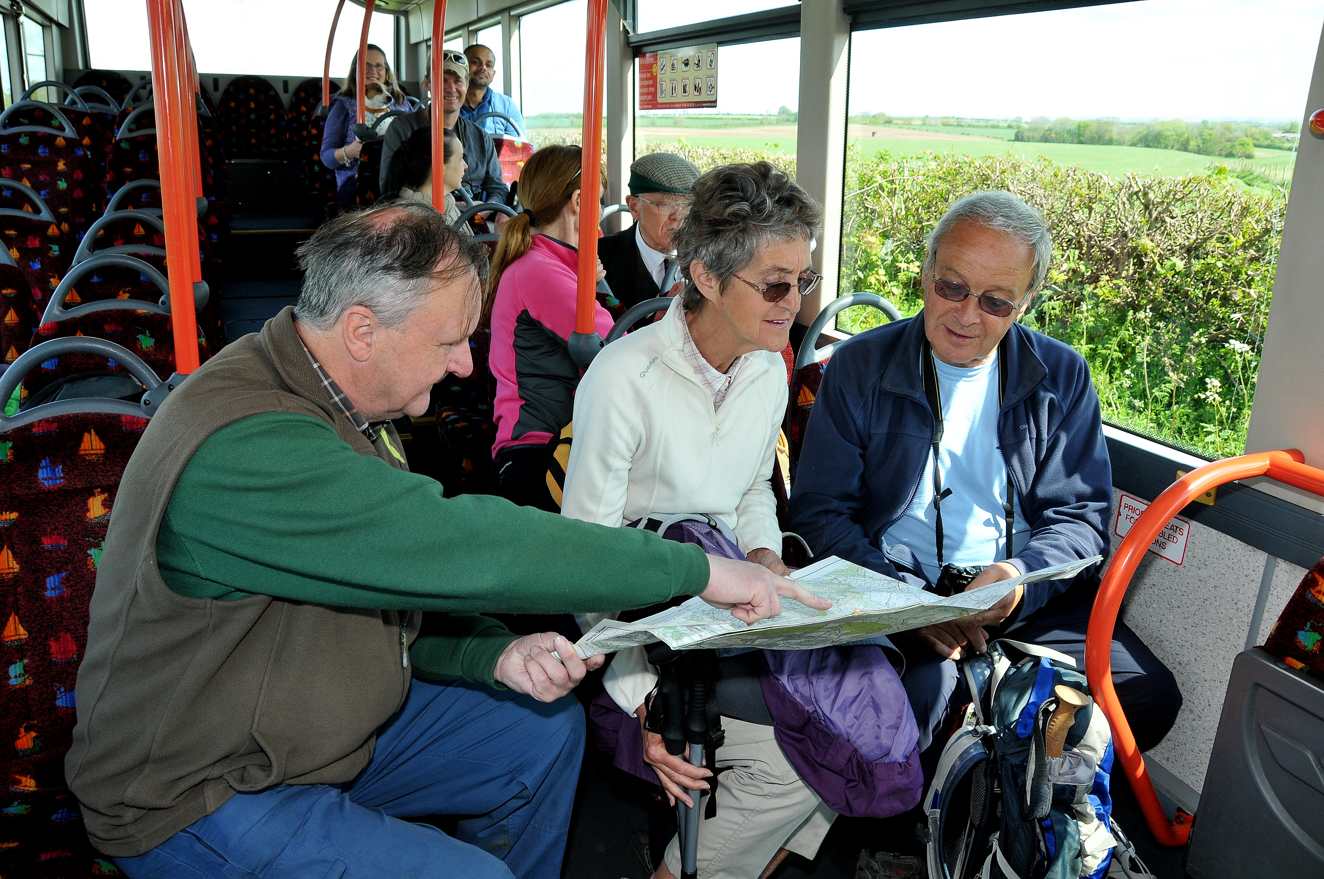 Walkers sit on a bus, looking at an ordance survey map