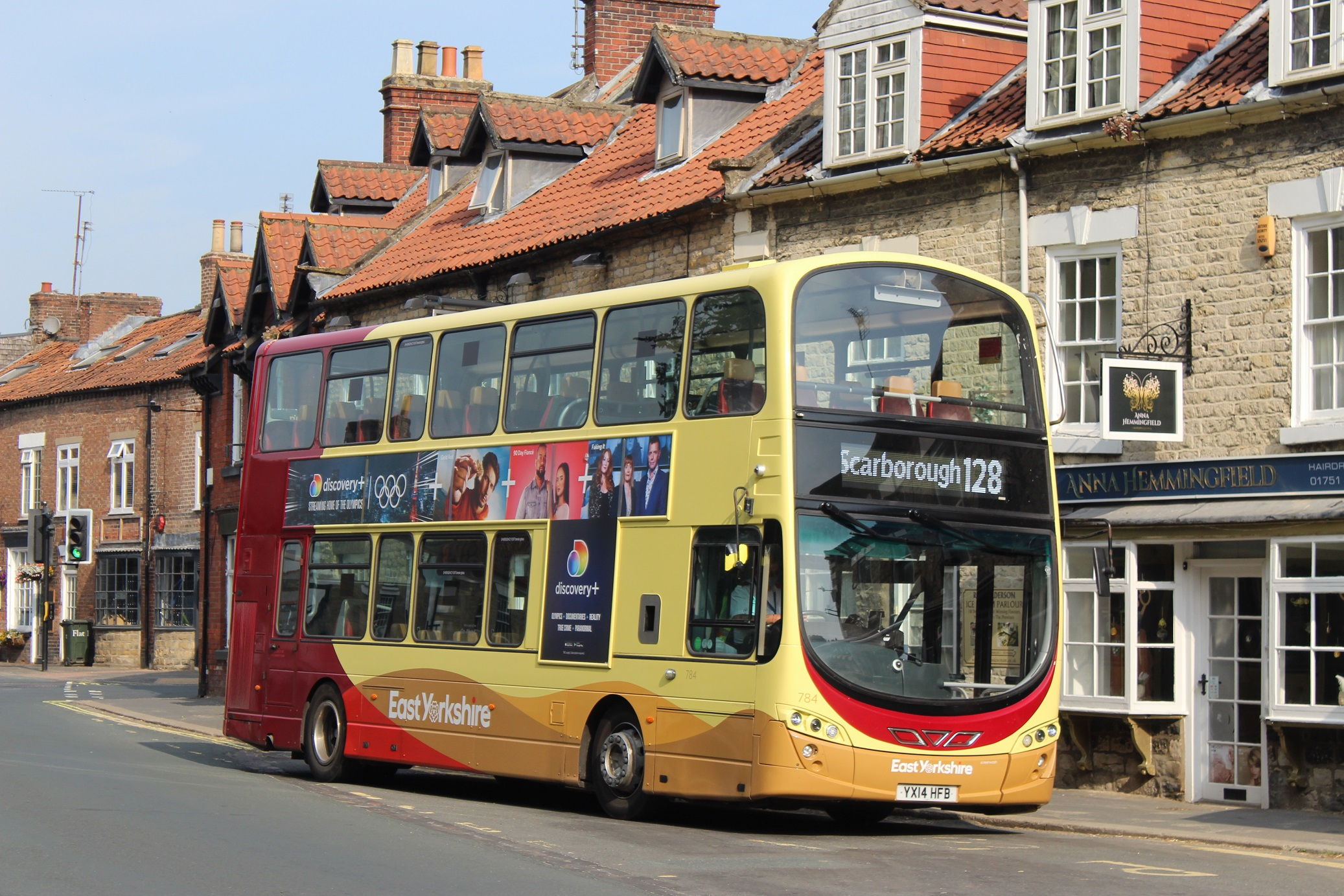 An East Yorkshire double decker Service 128 bus outside old buildings in Thornton Le Dale