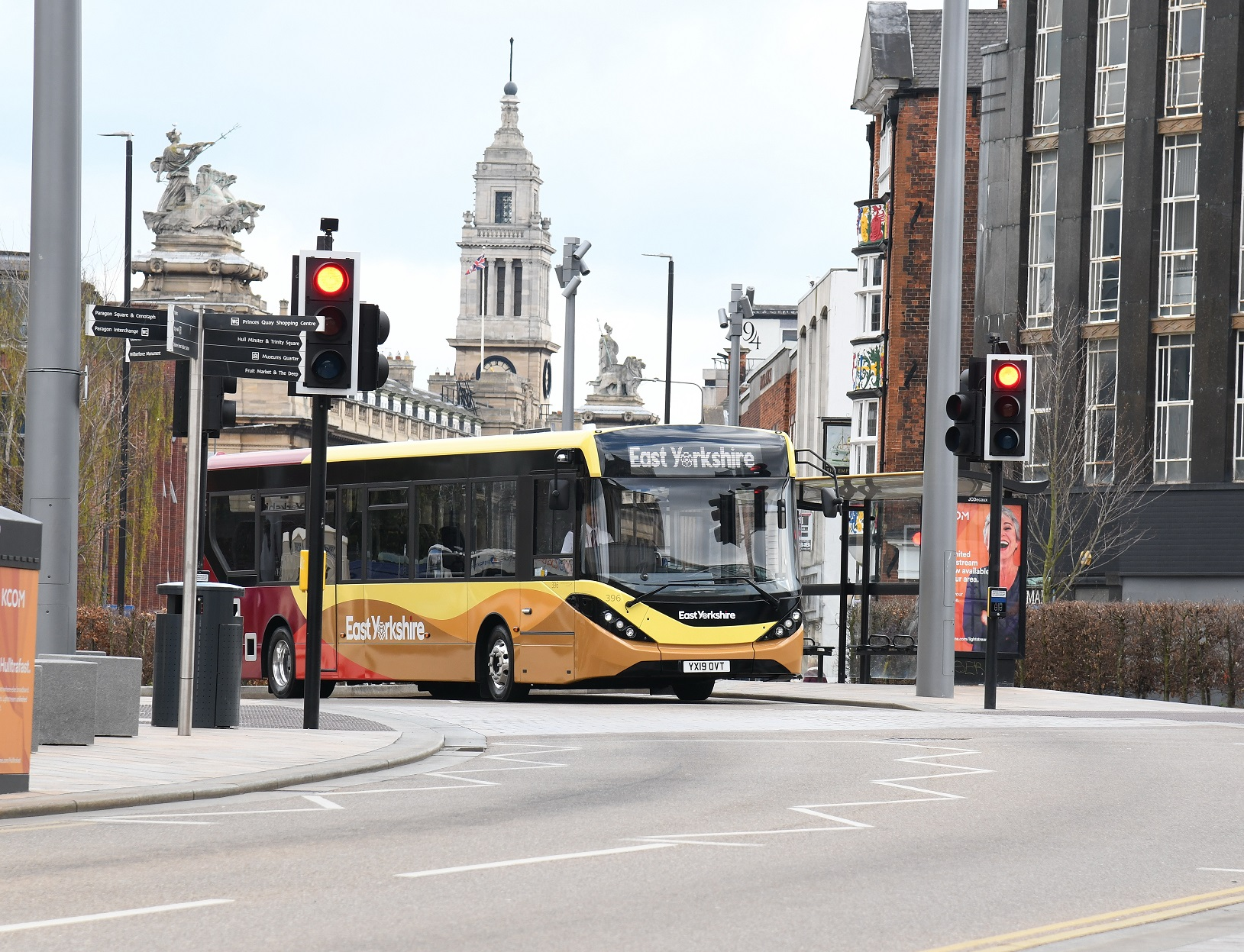 A single deck bus in Hull City Centre, with the Guildhall behind