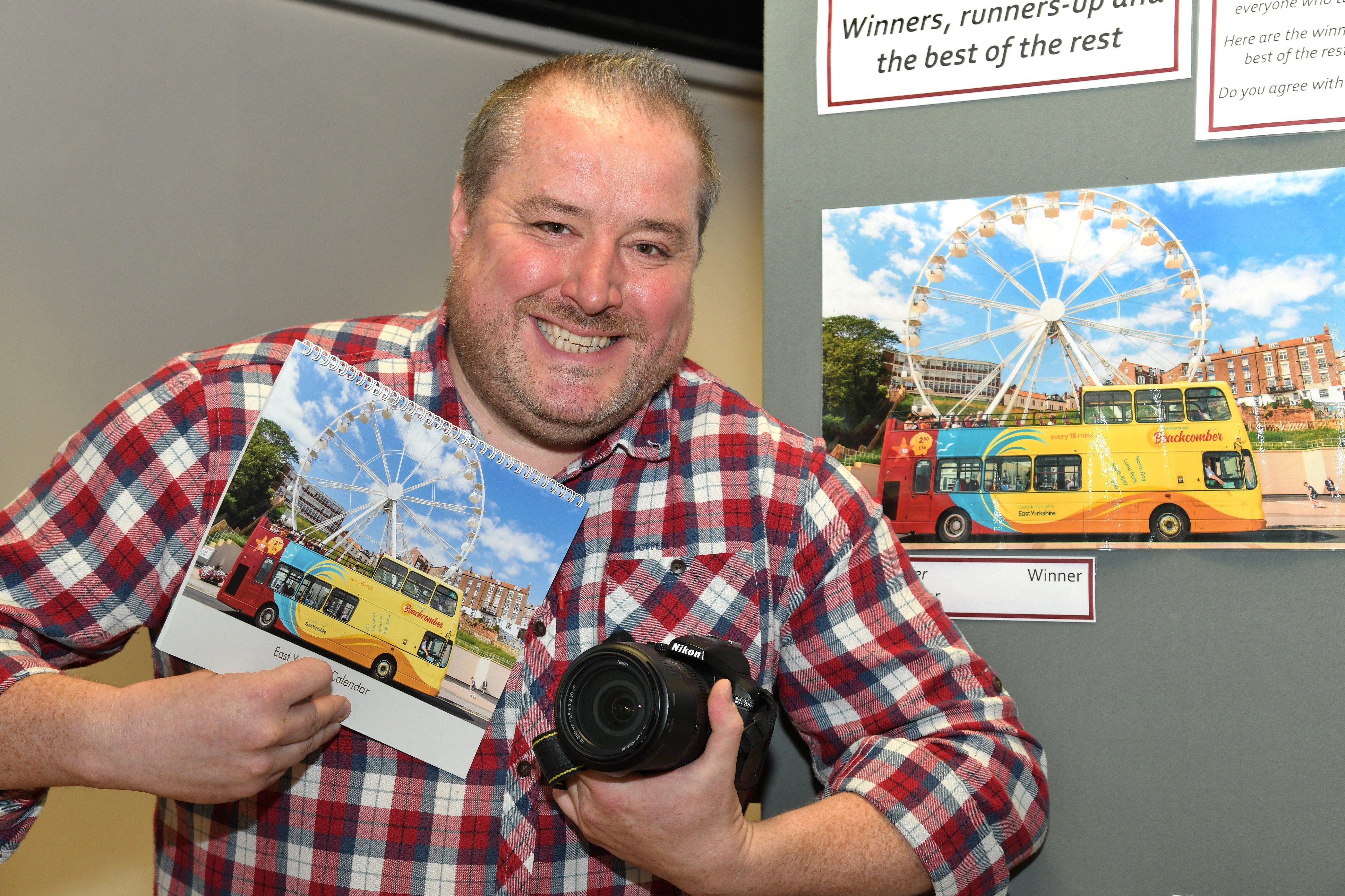 A man in a checked shirt holds a camera and a copy of his photograph, with a photograph exhibition behind him